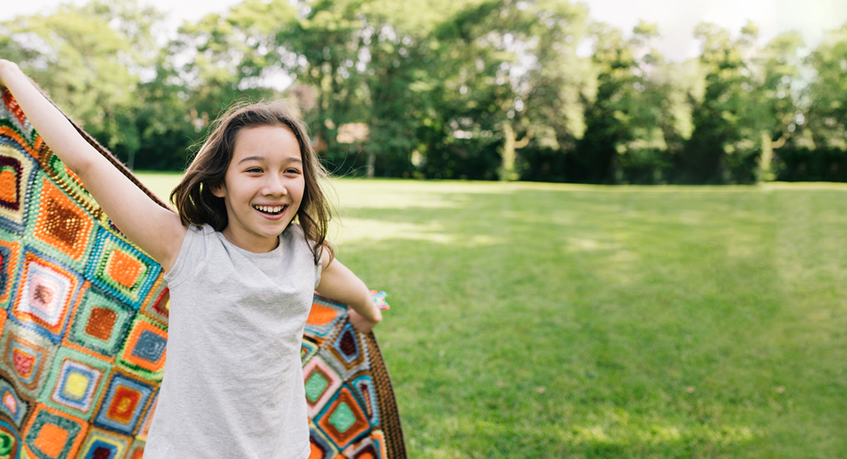 Smiling girl holding a colorful blanket outdoors