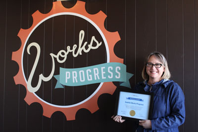 Works Progress owner Marnee Chua standing in front of Works Progress sign and holding Small Business of the Month award.
