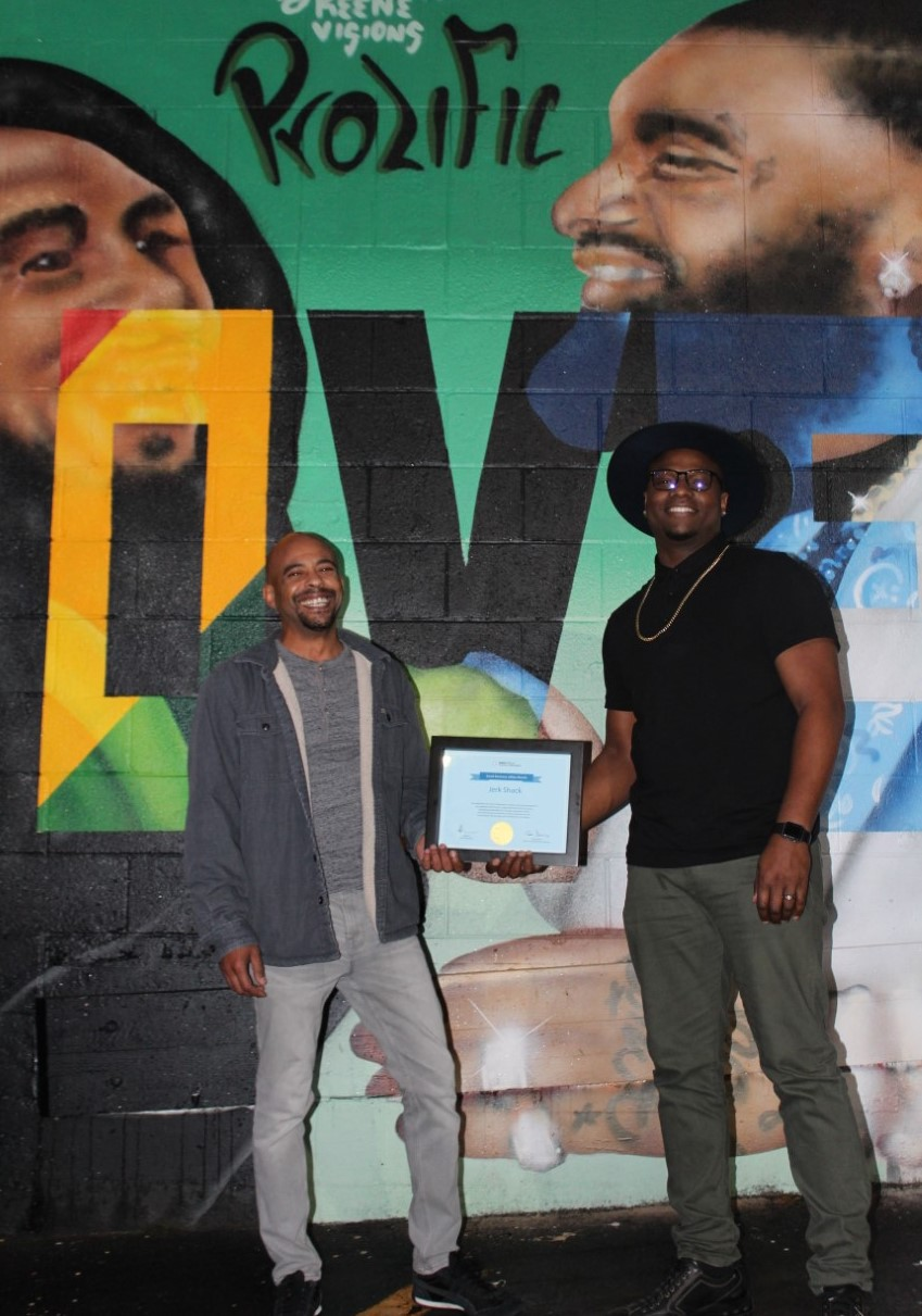 Owners Trey Lamont and John Devine in front of Jerk Shack with their small business of the month certificate