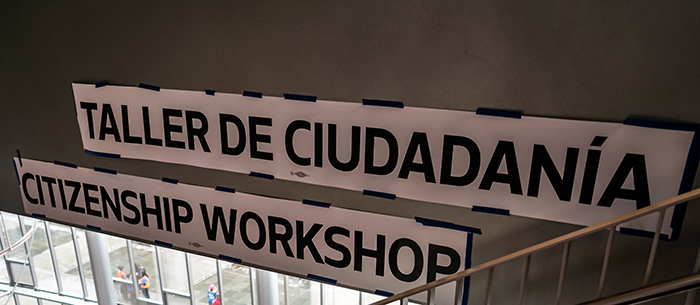 "Signs that read: ""Citizenship Clinic"" and ""Taller de Ciudadania."""