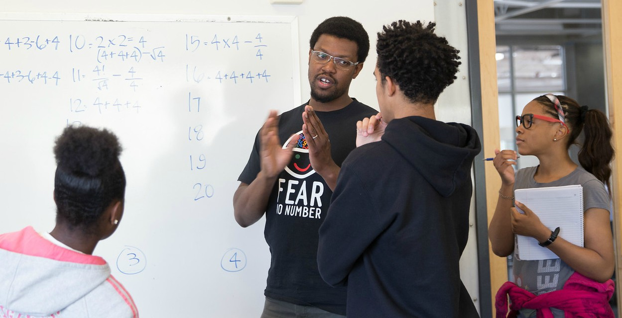 A teacher explains a math concept to his students at a DEEL funded math camp