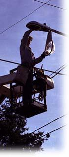 Photo of worker repairing streetlight.